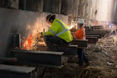 Sparks fly as workers smooth edges of brackets ahead of waler installation inside the station box.
