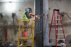 A welder cleans up the edges of welds on the steel jacket for a concrete column inside the north station entrance.